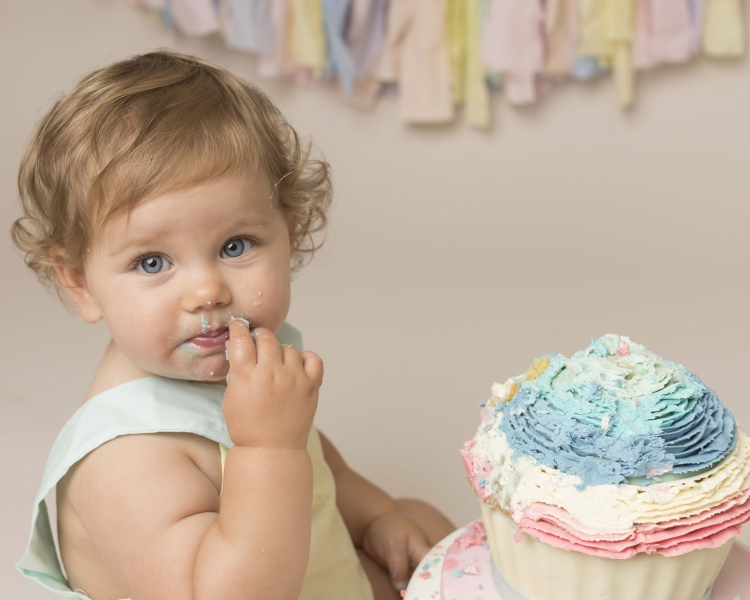 Girl eating cake during Cake Smash photo session in Hoylake