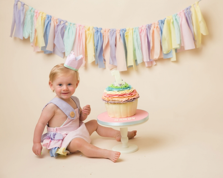 Pastel coloured cake smash with matching outfit and bunting