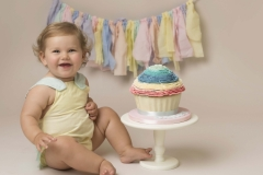 Girl enjoying her pastel coloured cake smash for her first birthday