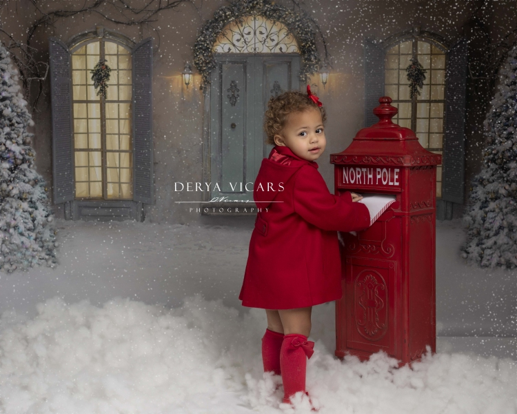 Christmas photoshoot with girl dressed in red posting a letter