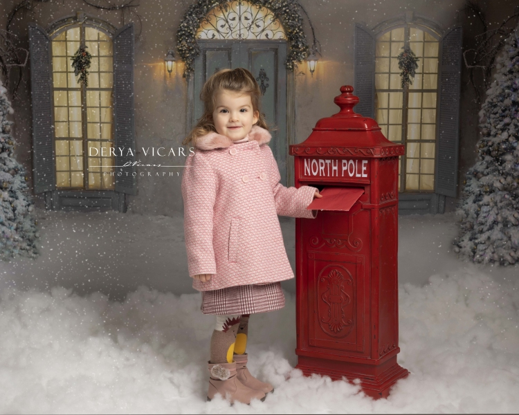 Girl at postbox in Christmas studio posting a letter