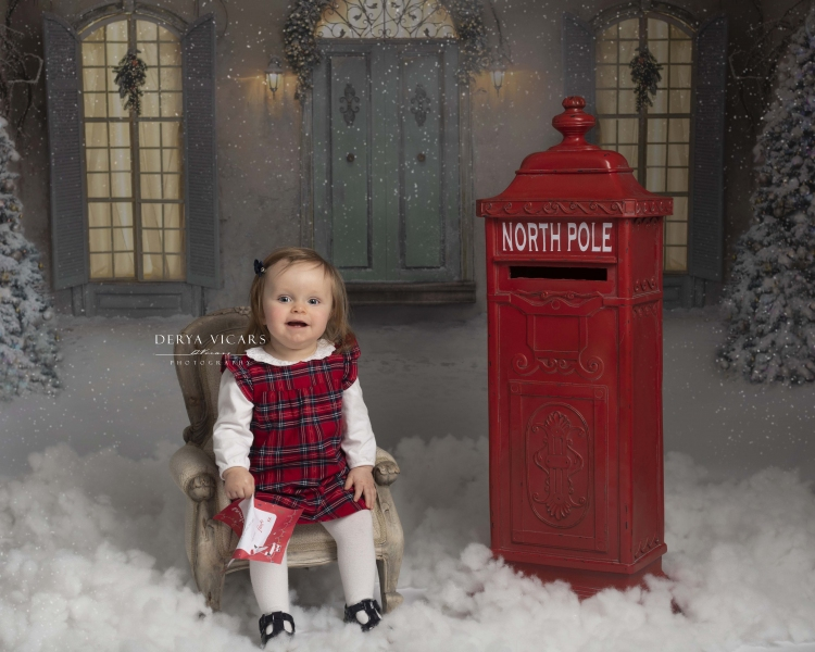 Girl sat in chair waiting to post letter to Santa at Christmas photo session in Wirral