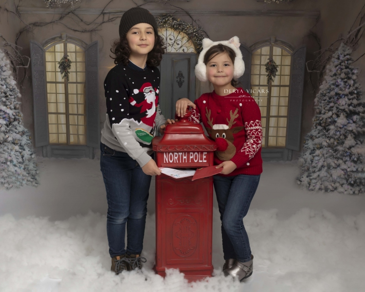 Two children delivering letters to father christmas in photoshoot at xmas time