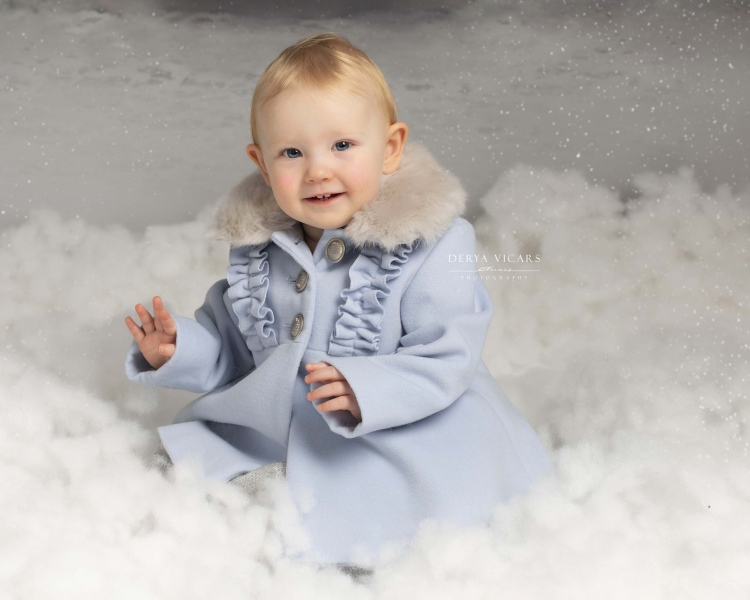 Girl in blue coat at photography studio in Heswall, Wirral at Christmas
