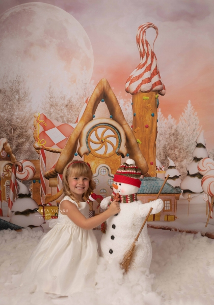 Little girl dressed in white in Heswall with a Snowman