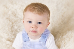 Boy in blue romper suit for child sitting session at Derya Vicars Photography Studio Wirral