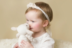Girl with cuddly toy at family photo shoot
