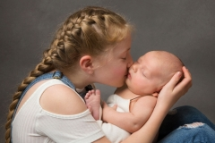 Girl kissing her sibling at Children Portrait and Family Photo Studio Wirral Merseyside