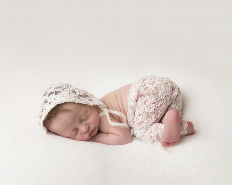 Bottom up pose with new born baby wearing white cotton lace effect clothes and hat
