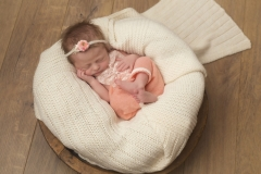 Overhead shot of baby in apricot coloured fabric in a bowl lined with white blanket - Serving Wirral and Cheshire