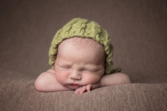 Baby in green textured hat on a brown background with head on arms - Saughall Massie Photo Studio