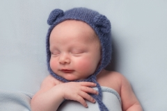 Baby in blue hat blanket and body wrap with arm over chest - Newborn Baby Pose Studio