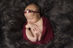 Baby with red head band snuggled in blankets - Wirral Photoshoot