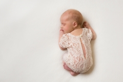 Baby with white lace baby grow on a white natural coloured blanket - Merseyside Photoshoot